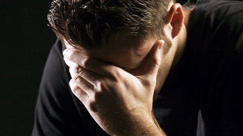 A young man holding his head with hands as in sorrow or remorse.