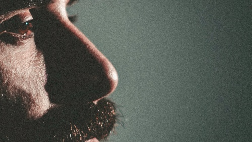A up close photo of a man's face and beard.