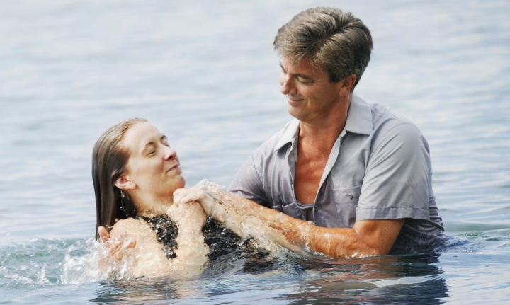 A man baptizing a woman after being fully submersed in the water.