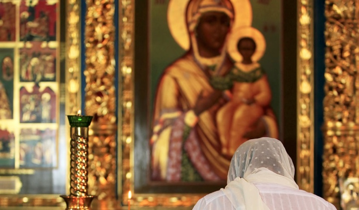 Woman praying to Mother Mary and baby Jesus painting.