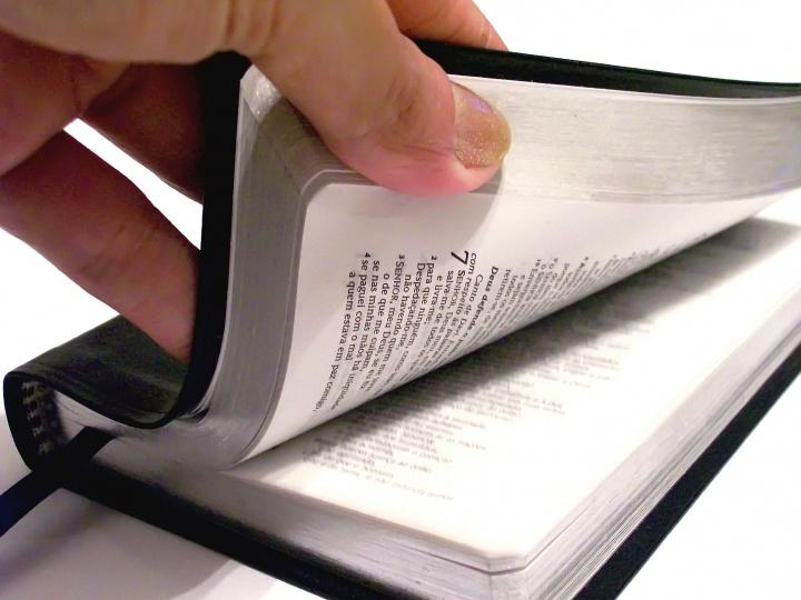 Una persona hojeando una Biblia